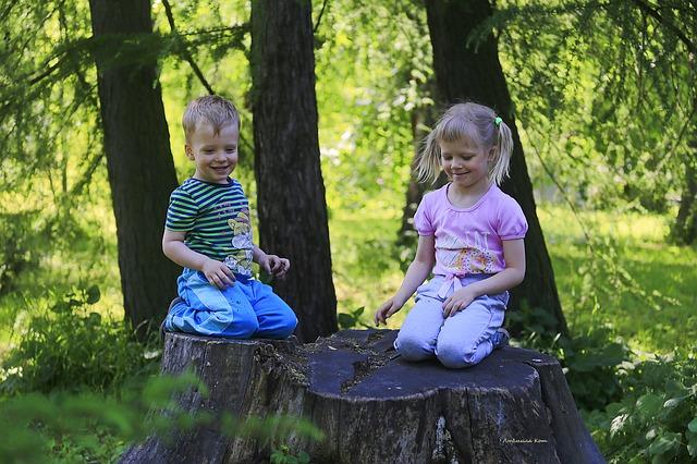 děti v lese, kluk a holka sedí na pařezu